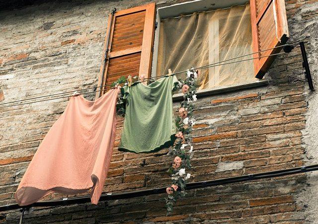 Wäsche auf einer Leine draußen vor einem Fenster